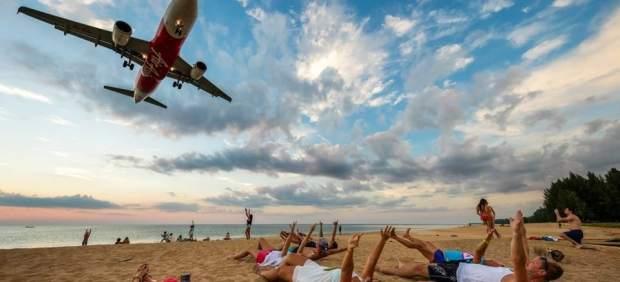 Aviones sobre turistas en la playa de Nai Yang