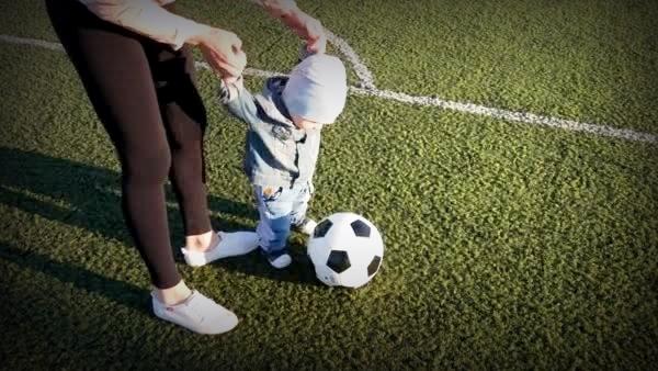 Una madre y un hijo jugando al fútbol.