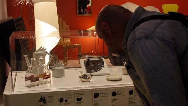 Un hombre observando nuevas piezas de la exposición 'Del Món al Museu' (Del Mundo al Museo), concretamente las botellas Ricard, en el Museu del Disseny de Barcelona.