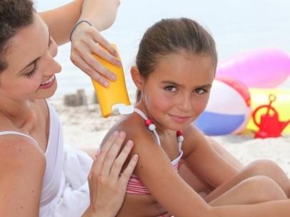 Una mujer aplica protector solar a una niña