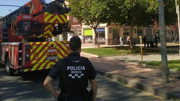 Un agente de la Policía de Murcia junto a un camión de bomberos.