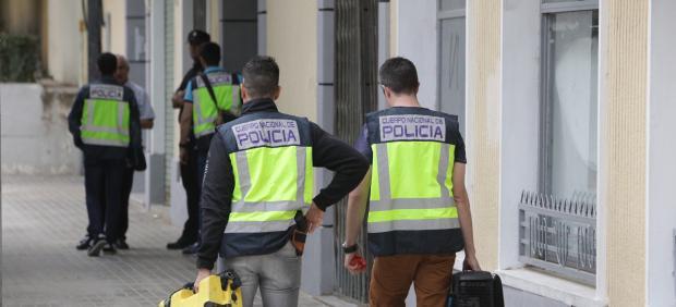 Agentes de Policía trabajan ante la vivienda de la mujer asesinada en Xàtiva