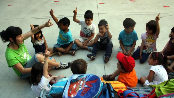 Niños junto a una monitora en el casal de verano de la escuela Fructuós Gelabert de Barcelona.
