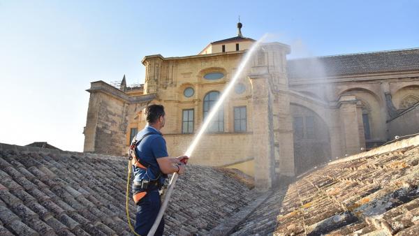 Un operario del equipo de mantenimiento del Cabildo participa en la prueba del sistema de extinción de incendios de la Mezquita-Catedral de Córdoba sobre el tejado de la misma
