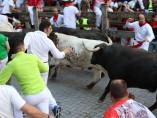 Decenas de personas corren en el cuarto encierro de las fiestas de San Fermín con toros de la ganadería Jandilla.