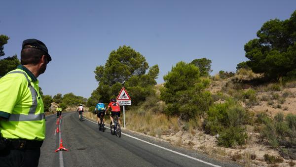 Guardias civiles observan a varios ciclistas .