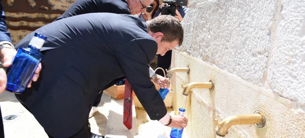 El presidente de C-LM, Emiliano García-Page, llena una botella de agua en la inauguración de 'Los baños de la reina' de Beteta (Cuenca).