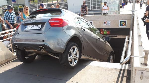 Imagen captada por un ciudadano del coche encastado en la boca de metro de Plaza España de Barcelona.