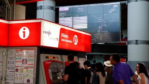 Unos viajeros sacan los billetes de tren en la estación de Atocha Cercanías