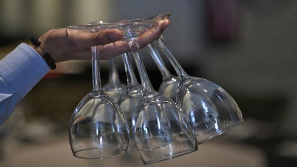 Un camarero sujeta copas de vino de cristal entre sus dedos.