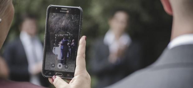 Una invitada a una boda fotografiando a los novios con su móvil
