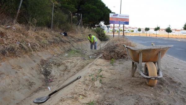 Operario del Ayuntamiento de Palos limpia una cuneta.