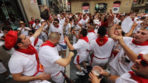 Cientos de personas disfrutan de la música y de los gigantes y cabezudos que animan las calles de Pamplona en plenos San Fermines de 2019.