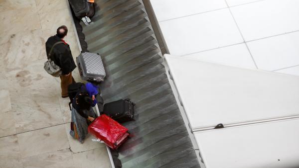 Un pasajero coge su maleta de la cinta transportadora,  junto a él, otro viajero espera a que llegue su maleta en el aeropuerto Adolfo Suárez Madrid-Barajas.