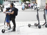 Un niño y un adulto montando en un patinete eléctrico en la calle Goya de Madrid.
