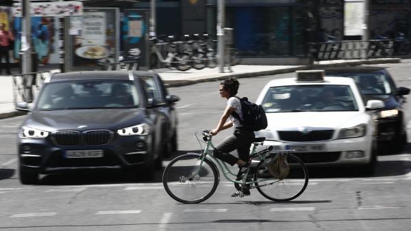 Una ciclista cruza por un paso de peatones en la Plaza de España de Madrid.