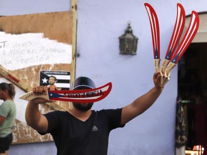 """Un vendedor ambulante muestra este miércoles una artesanía con el mensaje """"Ricky renuncia"""""""