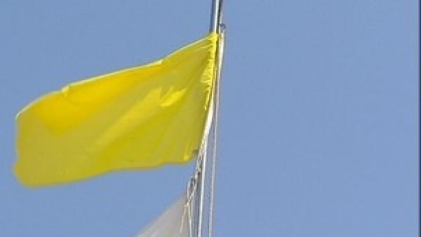 Una playa con bandera amarilla.