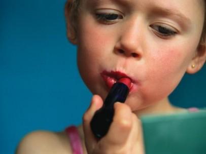 Una niña pequeña poniéndose pintalabios