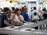 Varios pasajeros esperan en la cola de uno de los controles de El Prat.