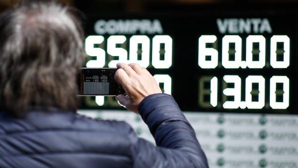 Un hombre toma una fotografía de los valores de compra y venta de la moneda argentina en Buenos Aires