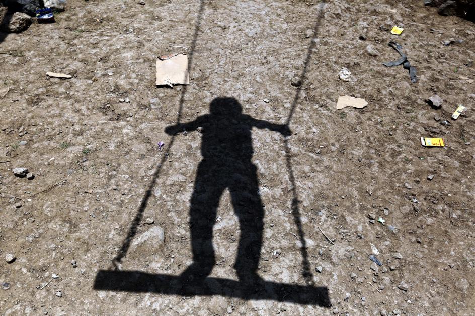 La sombra del juego. La sombra de un niño se proyecta en el suelo mientras juega en un columpio, en Saná (Yemen).