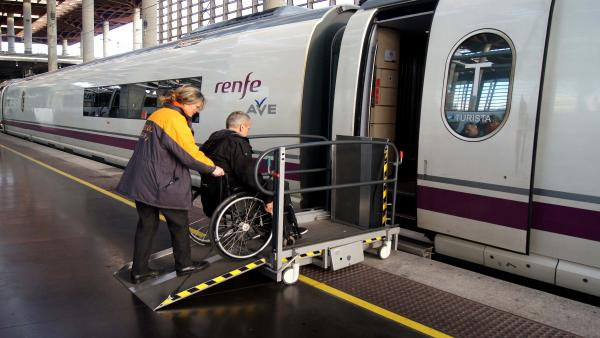 Servicio Atendo, personal ayuda a una persona con movilidad reducida a entrar en un tren AVE