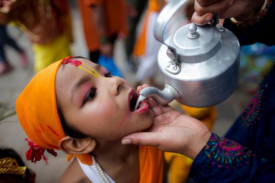 Leche sagrada. Un niño, con atuendo festivo, bebe leche de vaca antes de asistir a una procesión del 'Gai Jatra' ('Festival de la Vaca'), en Katmandú (Nepal).