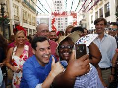 Moreno visita la Feria de Málaga y se fotografía con una turista.
