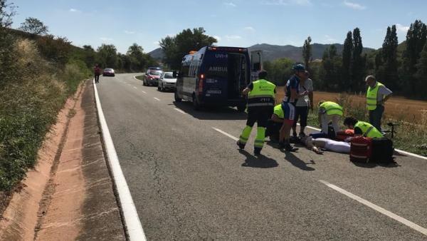 Personal sanitario atiende al ciclista que ha sufrido una caída.