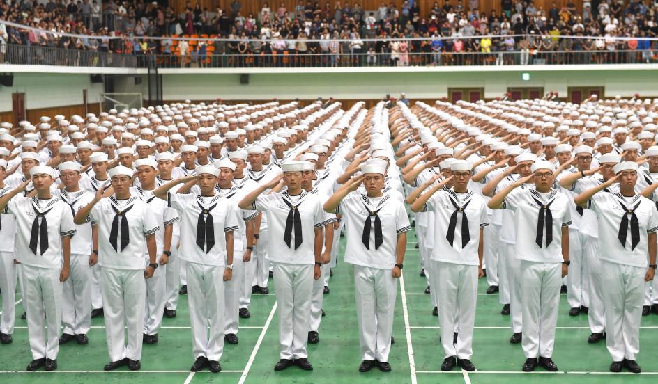 Todos a la vez. Los nuevos marineros saludan, después de completar la instrucción, en una ceremonia celebrada en el pabellón de la Base Naval de Jinhae (Corea del Sur).