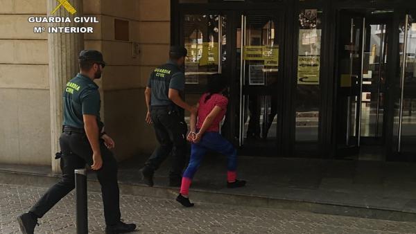 Un agente de la Guardia Civil detiene a una de las implicadas en el caso.