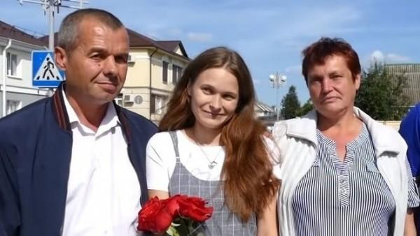 Yulia junto a sus padres biológicos