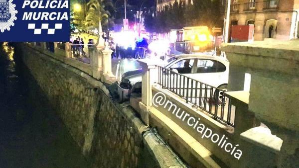 El coche tras chocar contra el muro a punto de caer al río Segura
