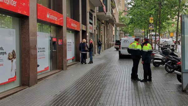 Agentes de Mossos d'Esquadra ante el edificio de la calle Comte Urgell de Barcelona donde se produjo el homicidio en mayo.