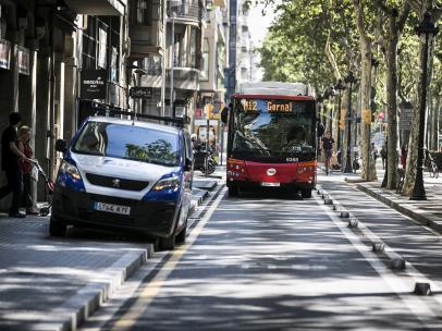 Un autobús urbano de Barcelona circulando por el carril bus lateral de la Gran Via con una furgoneta invadiendo parte de la calzada.