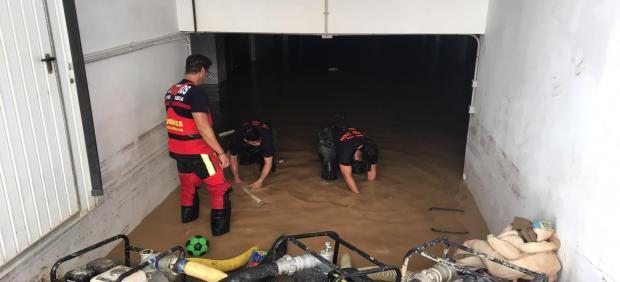 Voluntarios de Protección Civil y bomberos del CEIS trabajan en el achique de agua en un sótano de Los Alcázares
