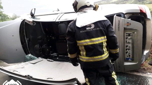 Un bombero frente al coche siniestrado en Venta de la Rana, en Villaviciosa.