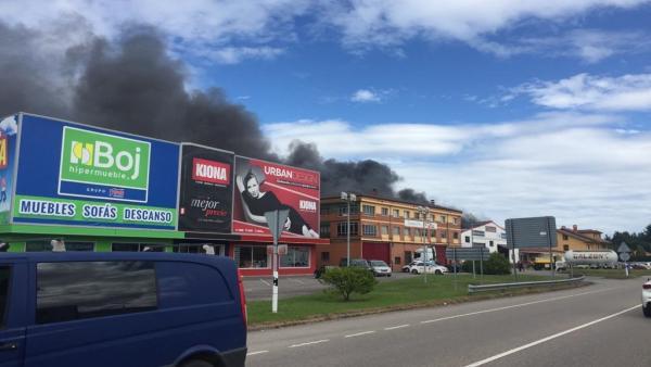Humo procedente del incendio de un taller en Siero.