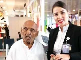 El monje hindú Swami Sivananda, de 123 años, haciéndose una foto con una empleada del aeropuerto