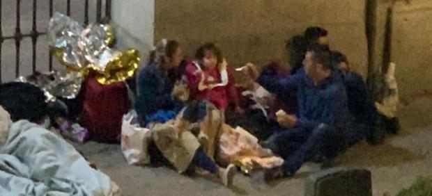 Imagen de una pareja con una menor pernoctando al raso frente a la sede del Samur Social.