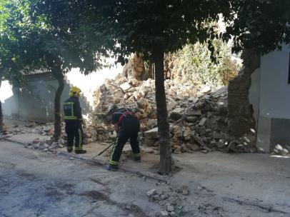 Dos bomberos junto al muro moderno y el trozo de muralla romana afectados por el derrumbe en la calle San Fernando de Córdoba.