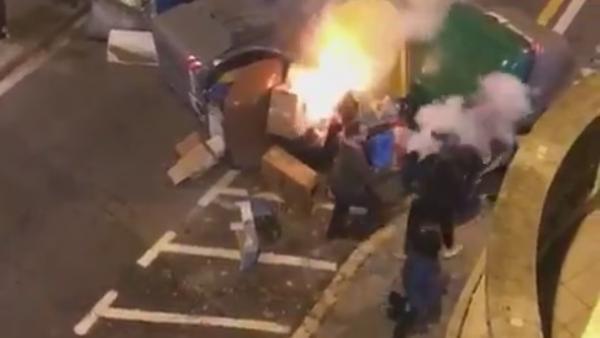 Intenta apagar un contenedor en llamas y lo apalean