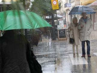 Varias personas se resguardan de una fuerte lluvia en Gandía